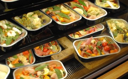 Retail cooler unit displaying a selection of ready to cook meals in aluminium trays - Plus Pack